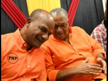 People's National Party Co-Campaign Director Peter Bunting (left) chuckles with party President Dr Peter Phillips at a meeting of councillors and councillor caretakers at The Mico University College.