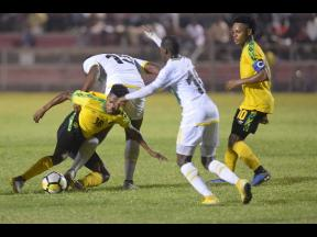 Jamaica's Nicque Daley (left) goes to ground after being tackled by Dominica's Peltier Kassim during their CONCACAF Under-23 Qualifier at the Anthony Spaulding Sports Complex in Kingston on Wednesday. Jamaican Alex Marshall (right) looks on. The game ended 1-1.