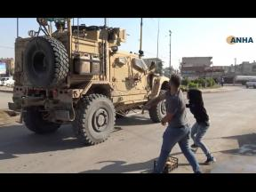 Residents who are angry over the US withdrawal from Syria hurl potatoes at American military vehicles in the town of Qamishli, northern Syria, yesterday.