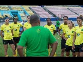 Former Reggae Girlz Head Coach Hue Menzies (back to camera) interacts with several members of the team during a training session held at the National Stadium on May 13, 2019.
