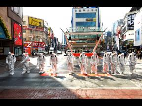 South Korean army soldiers wearing protective suits spray disinfectant to prevent the spread of the COVID-19 virus on a street in Daegu, South Korea, yesterday. As the worst-hit areas of Asia continued to struggle with a viral epidemic, with hundreds more cases reported Thursday in South Korea and China, worries about infection and containment spread across the globe.