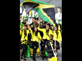 Jamaica's Usain Bolt (foreground) carries his country's flag during the Opening Ceremony of the 2012 Olympic Summer Games at the Olympic Stadium in London, Friday, July 27, 2012.