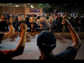 Protesters raise their fists during a rally in Las Vegas on Monday over the death of George Floyd, a black man who died in police custody in Minneapolis.