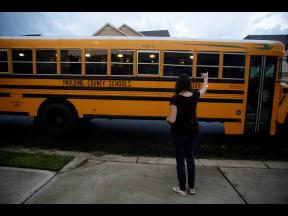 Rachel Adamus waves goodbye to her two children, Paul and Neva, as they ride the bus for the first day of school yesterday in Dallas, Georgia.