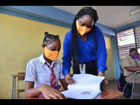 Grade 11 coordinator at Pembroke Hall High, Jodi-Ann Carnegie, assists fifth-form student Tasheika Messam with her work on Monday, June 8, 2020. Schools reopened for sittings of regional examinations ahead of the summer holidays. Education Minister Fayval