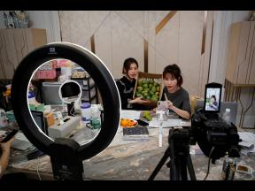 In this May 5, 2020 photo, China's online celebrity Zhang Mofan, right, introduces fresh mangos to her online clients and fans through livestreaming at her house in Beijing.