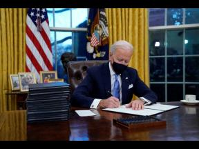 President Joe Biden signs his first executive order in the Oval Office of the White House on Wednesday, January 20, in Washington.