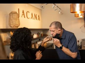 Industry and Investment Minister Audley Shaw gets a whiff of Jacana's buds from one of the store's client experience representatives.