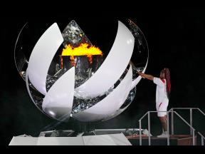 Naomi Osaka lights the Olympic flame during the opening ceremony in the Olympic Stadium at the 2020 Summer Olympics in Tokyo, Japan, yesterday.