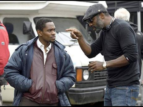 Aml Ameen (left) taking directions from Idris Elba during the filming of 'Yardie'.