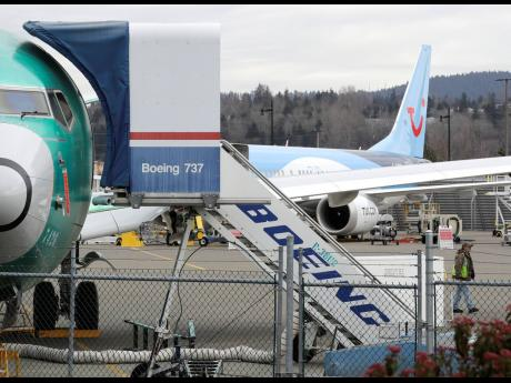 In this photo taken  on Monday, March 11, 2019, a Boeing 737 MAX 8 airplane being built for TUI Group sits parked in the background at right at Boeing Company's Renton assembly plant in Renton, Washington.
