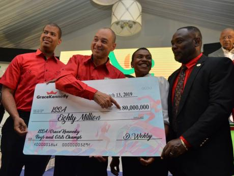 Don Wehby (second left), GraceKennedy's Group Chief Executive Officer, hands over a presentation cheque representing the company's $80 million sponsorship of the ISSA/GraceKennedy Boys and Girls Athletics Championships to ISSA president Dr. Walton Small (right) at the event's launch at the Spanish Court Hotel yesterday. Looking on is Frank James, GraceKennedy's Group Chief Financial Officer (left) and Colleen Montague Chairman of the Organising Committee.