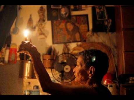 "Seventy-two-year-old Elizabeth Guzmán Espitia holds a candle in the windowless room she calls her ""little cave"" during a blackout in the Santa Cruz of the East neighbourhood in Caracas, Venezuela, on Thursday, March 14."" I've never see a crisis like this. It's the first time,"" Guzmán Espitia said."