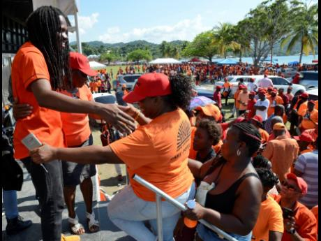 Damion Crawford (left) greets supporters shortly after he addressed them at Folly Oval on nomination day, March 15, for the April 4 by-election.