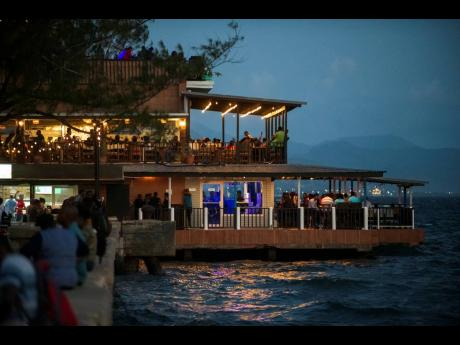 Scores of patrons enjoying an evening at the Victoria Pier, downtown Kingston, on January 25. The renovated pier houses eateries and entertainment venues and has become a regular spot for parties.