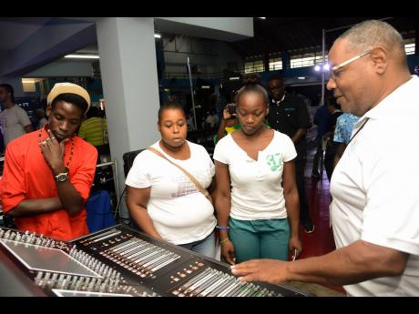 Ricardo Aikman (right), audio engineer at Main Event Entertainment Group, explains the workings of a mixer board to Richard Shay (left), Kerry-Ann Wilson (second left), and Sheneil Sterling. The showcase was part of yesterday's media launch for Main Event's M-Academy, a training institution to certify individuals in the areas of audio, lighting, and video.