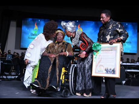 Rita Marley (seated) receives a kiss from fellow members of the I-Three, Judy Mowatt (left) and Marcia Griffiths (second right), while Minister of Culture, Gender, Entertainment and Sports Olivia 'Babsy' Grange looks on. Occasion was the Reggae 50 Awards during February's Reggae Month celebrations.