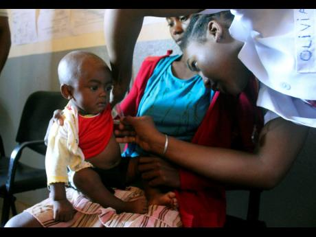 A volunteer nurse examines a six-month-old child, who is infected with measles, while her mother looks on, at a healthcare centre in Larintsena, Madagascar.