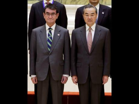 Japanese Foreign Minister Taro Kono (left), and China's Foreign Minister Wang Yi attend a group photo event before the Japan-China high level economic dialogue at Diaoyutai State Guesthouse in Beijing, China yesterday.