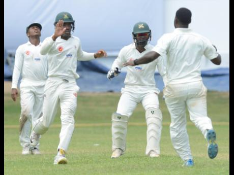 Members of the Melbourne Cricket Club celebrate the dismissal of a Jamaica Defence Force batsman during the Jamaica Cricket Association Senior Cup final at Sabina Park on Saturday.