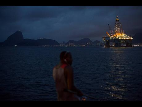 AP In this April 21, 2015 file photo, a man fishes near a floating oil platform in Guanabara Bay in Niteroi, Brazil. The administration of Jair Bolsonaro plans to auction seven oil fields despite contrary advice from analysts of Brazil's main environmental body.