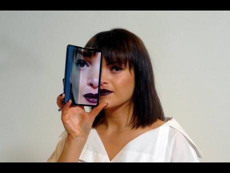 AP A model holds a Samsung Galaxy Fold smartphone to her face during a media preview event in London, on Tuesday, April 16.