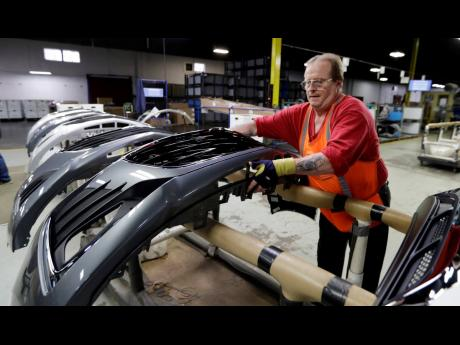 AP This November 28, 2018 file photo shows Clifford Goff, a bezel assembler, transferring a front end of a General Motors Chevrolet Cruze during assembly at Jamestown Industries in Youngstown, Ohio.