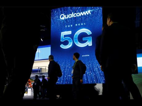In this January 9, 2019 file photo, a sign advertises 5G at the Qualcomm booth at CES International in Las Vegas. Apple and mobile chipmaker Qualcomm have settled a bitter financial dispute centered on some of the technology that enables iPhones to connect to the Internet.