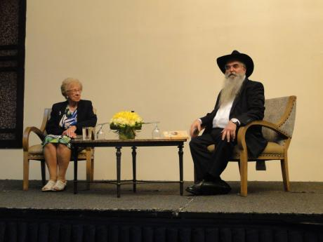 Holocaust survivor Eva Schloss looks at moderator, Rabbi Zush Wilhelm, as he listens to a question from the audience during an interview at The Jamaica Pegasus on Tuesday, April 2.