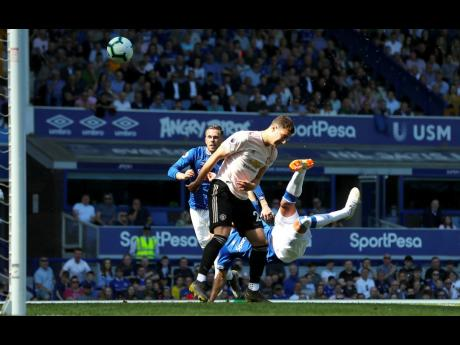 Everton's Richarlison (right) scores against Manchester United during their English Premier League match at Goodison Park, Liverpool, England yesterday.