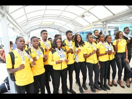 Some members of Jamaica's team to the Carifta Games in the Cayman Islands pose shortly after their return to the island at the Norman Manley International Airport yesterday.