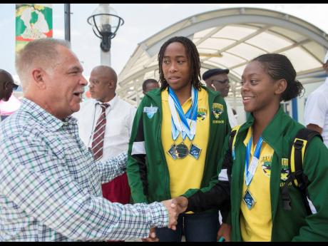 Martin Lyn (left) President, Amateur Swimming Association of Jamaica, congratulates Karci Gibson (right) and Brianna Anderson, who were among the Jamaican team members, who returned to the island yesterday at the Norman Manley International Airport, from the 2019 Carifta Swimming Championships in Barbados.