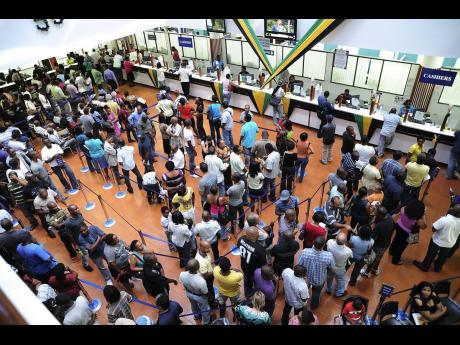 Customers queue to conduct business at a local tax office in this 2012 Gleaner photo.