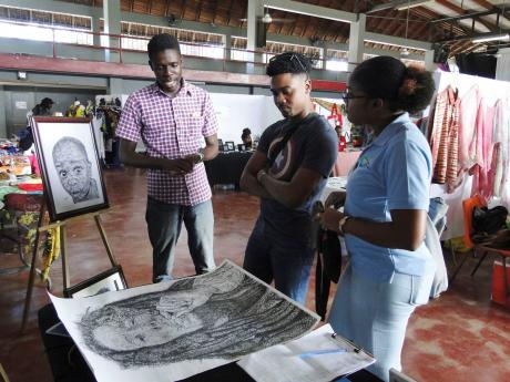 Artist Kuruma Reid talking about his art with Jamaro Marville and Yonique Priestley, officers from the Tourism Enhancement Fund, at the recent Craft Craft Jamaica Pop-Up Craft Village at Campion College in St Andrew.