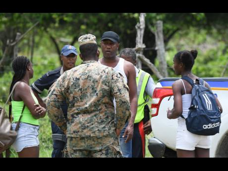 Jamaica Constabulary Force and Jamaica Defence Force personnel confront a man at a checkpoint in Whitehouse, Westmoreland, on day three of the state of public emergency on Thursday. The security crackdown was declared in Hanover, St James, and Westmoreland, the parishes with the highest per-capita incidence of murder, outside of the Corporate Area, in 2019. Ricardo Makyn/Chief Photo Editor