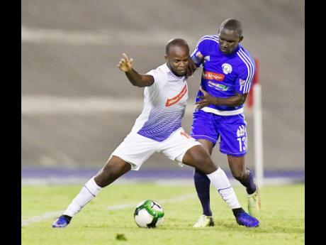 Portmore United's Javon East (left) keeps Xavian Virgo of Mount Pleasant FA off the ball during the second leg of their Red Stripe Premier League semi-final at the National Stadium on Monday, April 15, 2019.