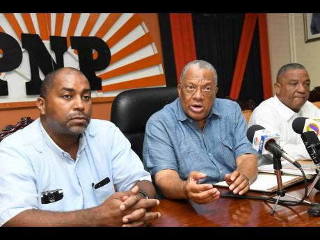 People's National Party President Dr Peter Phillips (centre) addresses the media while General Secretary Julian Robinson (left) and Horace Dalley look on at a press conference at the party's Old Hope Road headquarters in St Andrew yesterday.