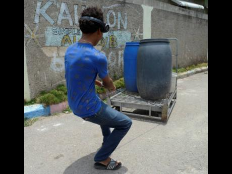 A resident of Waterhouse in St Andrew uses a makeshift cart to transport two barrels and a bucket of water yesterday.