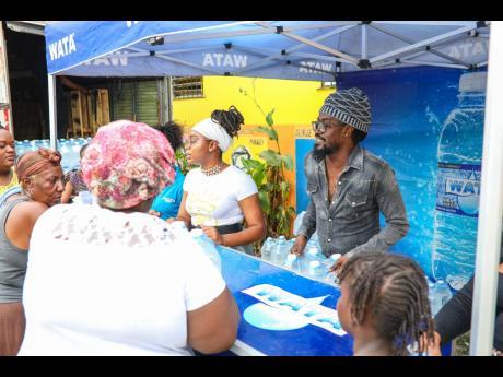 Moses 'Beenie Man' Davis, alongside partner Krystal Tomlinson, distributes bottles of Wata to residents of Waterhouse, St Andrew.