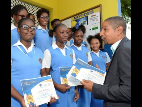 Delroy Williams (right), mayor of Kingston, congratulates students at Merl Grove High School at the awards and launch ceremony of the Children Experiencing Everyday Transformation programme at the school, which uses literature to transform underperforming and undisiplined children into better students.