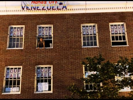 An activist who supports Venezuelan Nicolás Maduro stands by the window of the Venezuelan embassy in Washington on Monday, May 13, 2019. AP