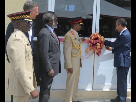 National Security Minister Dr Horace Chang (right) and Lt Gen Rocky Meade (second right) cut the ribbon to officially open the Jamaica Defence Force's Burke Barracks in Flankers, Montego Bay, St James, yesterday. Also sharing in the occasion are (from left) Lt Col Godphey Sterling, commanding officer for the Second Battalion, The Jamaica Regiment; Peter Melhado, chairman of WIHCON; Dr David Stair, custos of Hanover.