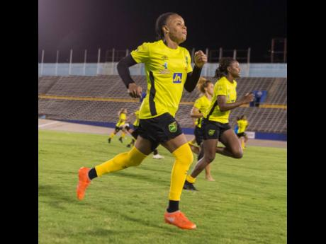 Trudi Carter (left) goes through her paces along with Konya Plummer (right) and other members of the Reggae Girlz squad during a training session at the National Stadium on Monday ahead of the team's international friendly against Panama scheduled for May 19 at the same venue.