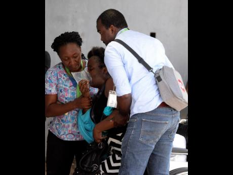Two persons assist a woman into an ambulance yesterday morning after mysterious fumes caused some workers at the South Camp Road-based Central Sorting Office to fall ill with irregular breathing and fainting spells. Operations at the post office were suspended for the remainder of the day, while those at the Sutherland Global call centre on the compound were resumed after receiving clearance from the Jamaica Fire Brigade.