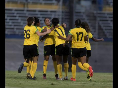 National striker Khadija Shaw (11) celebrates a goal with teammates during their friendly international match against Panama at the National Stadium last night.