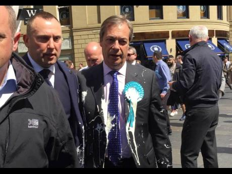 Brexit Party leader Nigel Farage (right) after being hit with a milkshake during a campaign walkabout for the upcoming European elections in Newcastle, England, yesterday.