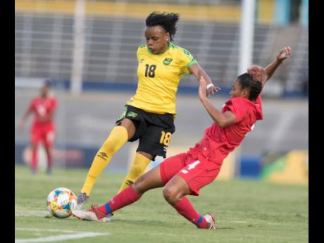 Trudi Carter (left) of Jamaica rides a challenge from Katherine Castillo of Panama during a friendly international between Jamaica and Panama at the National Stadium on Sunday. Jamaica won 3-1.