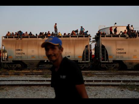 In this April 23, 2019 file photo, Central American migrants ride a freight train on their way to the US-Mexico border in Ixtepec, Oaxaca state, Mexico.