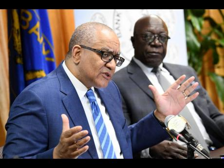 Governor of the Bank of Jamaica (BOJ) Brian Wynter gestures during his quarterly press conference at the BOJ headquarters in Kingston on Tuesday, May 21, 2019. Senior Deputy Governor John Robinson is at right.