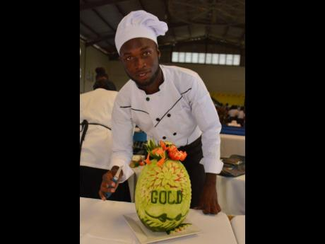 Chef Kimarley Russell, possess with his gold medal-winning fruit carving, at a previously held Eastern Regional Culinary Championship.